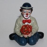 Florius, hockend, rote Blumen